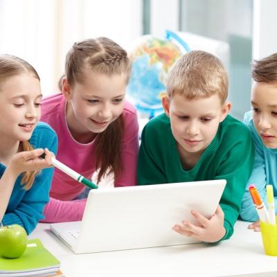 Portrait of smart schoolgirls and schoolboys looking at the laptop in classroom